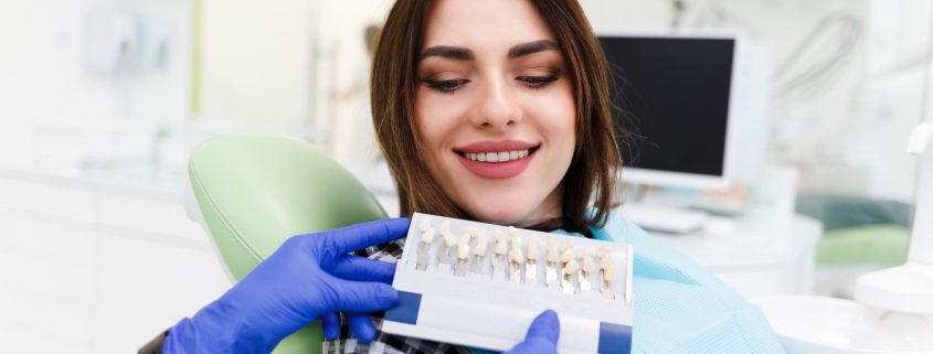 dentist-his-patient-choose-tone-veneers-dentistry-doctor-shows-palette-with-shades-teeth_38