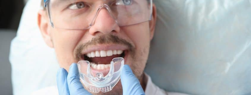 Dentist trying on mouthguard for man patient